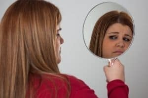 lady looking unhappily at herself in the mirror