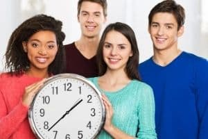 Teenagers holding a clock